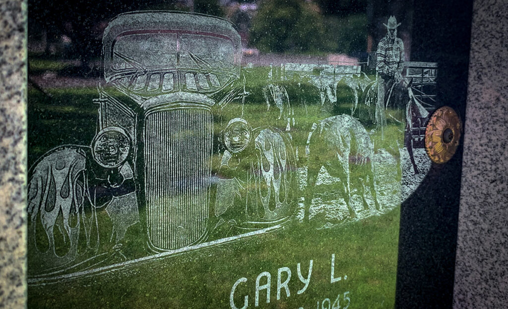 Etchings in white on black granite show a hot-rod truck and a man on horseback herding cattle.