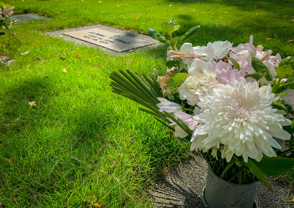 Flush marker in grass with a vase of white mums.