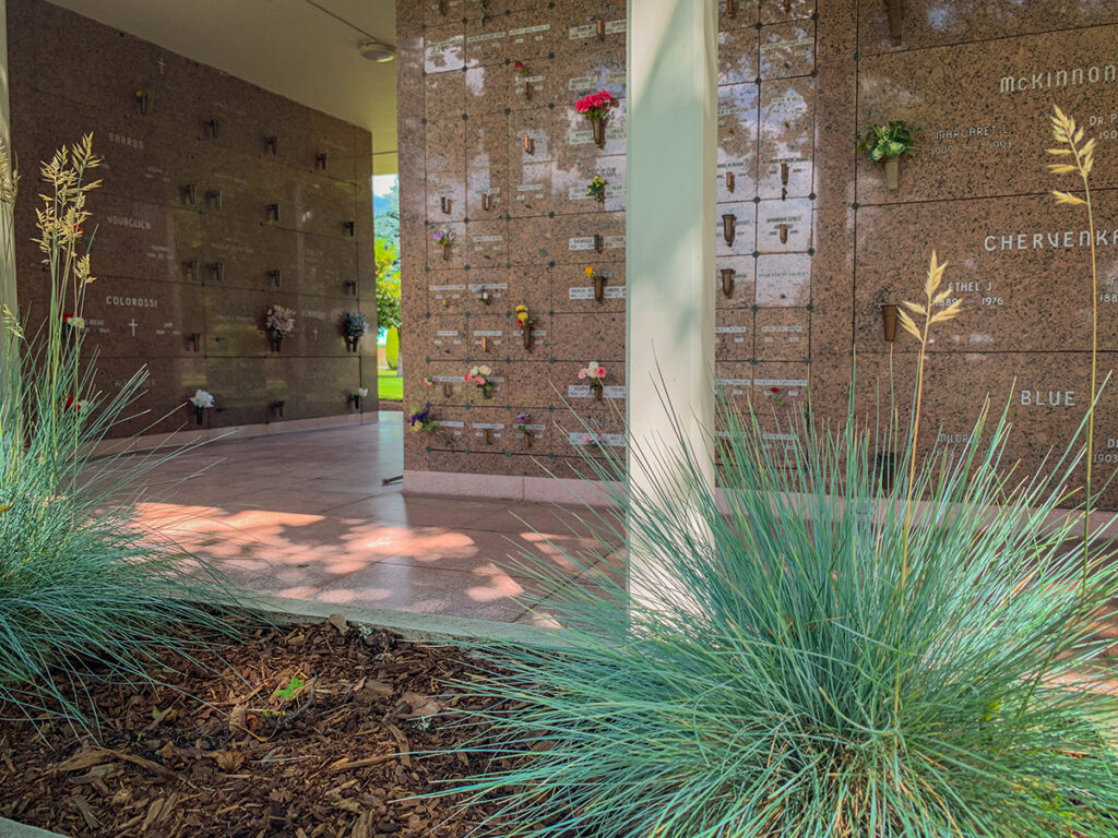 Outdoor walls of granite with a tile path in front and bluegrass planted in foreground.