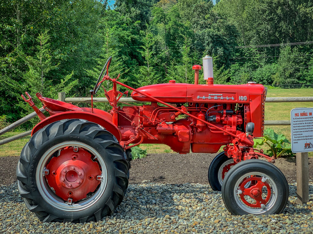 Red Farmall tractor sits on a bed of gravel with trees in the background.