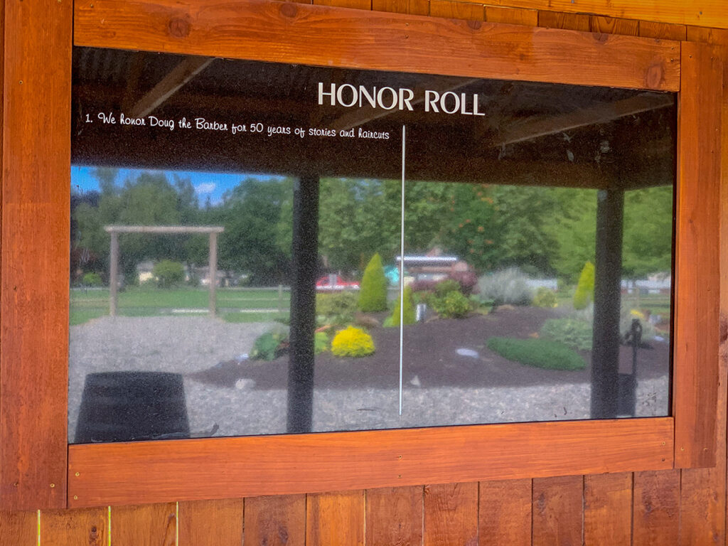 Honor Roll in black granite with white letters etched and a wood frame. Heritage Farm is reflected off the black granite.