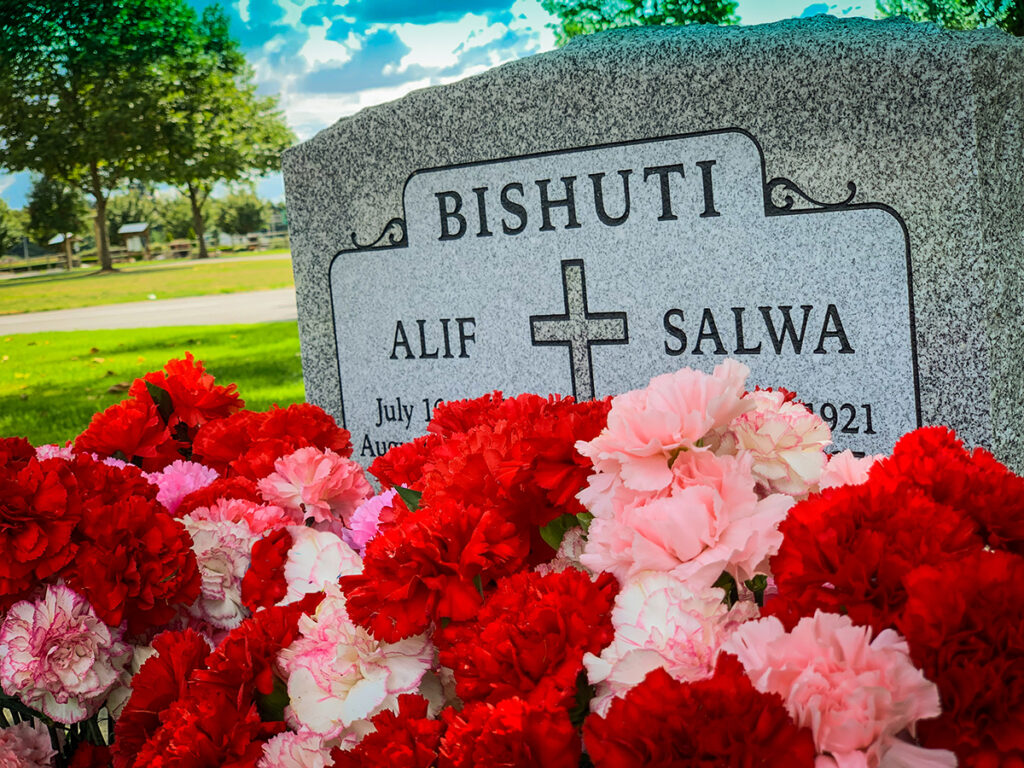 Granite marker for Bishuti, Alif and Salwa with a cross and red and pink carnations in front.
