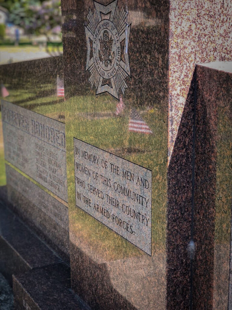 Granite memorial reads In memory of the men and women of this community who served their country in the Armed Forces.
